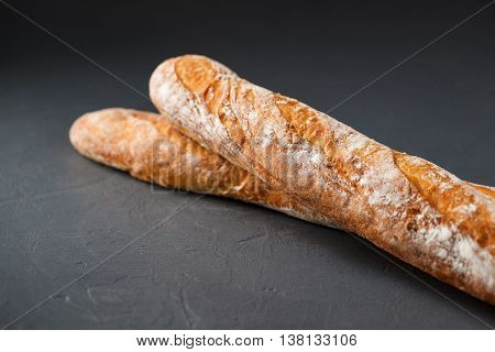 Cropped photo of two french baguettes on gray textural background, selective focus