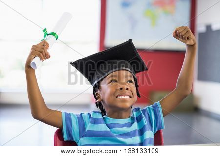 Excited schoolboy in mortar board holding certificate in classroom at school