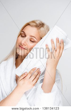 Portrait of blonde young pretty girl in bathrobe, holding towel, smiling, eyes closed, over white background.