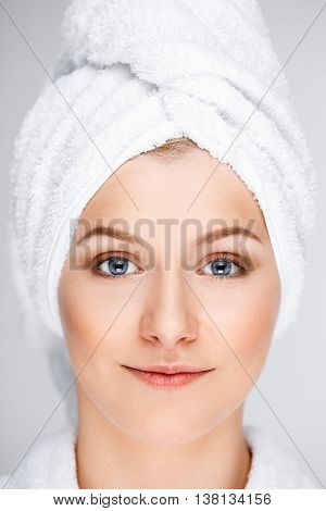 Close up portrait of blonde young pretty girl in bathrobe with towel on head, smiling, looking at camera, over white background.