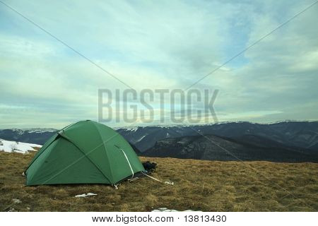 Green tent on grassland in Crimean mountain