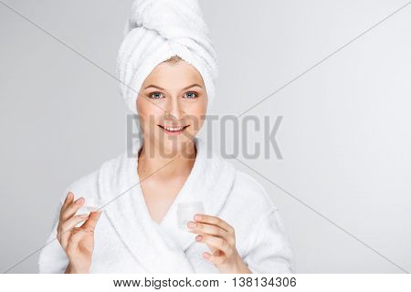 Portrait of blonde young pretty girl in bathrobe with towel on head, opening cream, smiling, looking at camera, over white background.