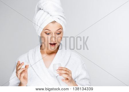 Portrait of blonde young pretty girl in bathrobe with towel on head, opening cream, surprised, over white background.