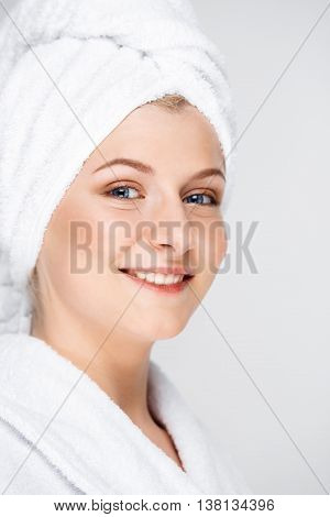 Portrait of blonde young pretty girl in bathrobe with towel on head, smiling, looking at camera, over white background.