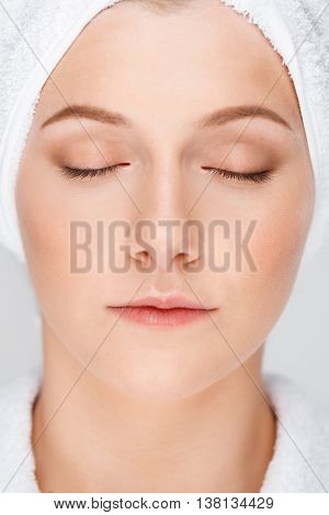 Close up portrait of blonde young pretty girl in bathrobe with towel on head, eyes closed, over white background.