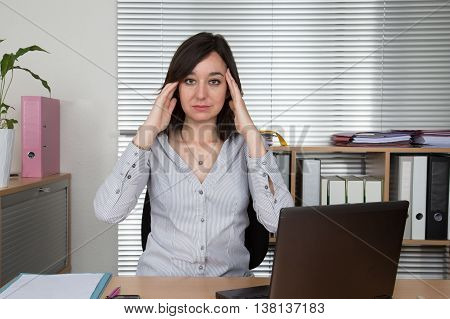 Exhausted Businesswoman In Her Office With Head In Hands