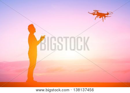 silhouette of one man use a drone in the night