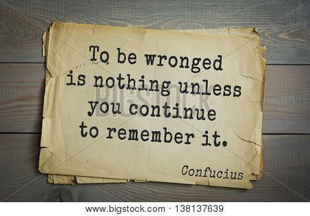 Ancient chinese philosopher Confucius quote on old paper background. To be wronged is nothing unless you continue to remember it.