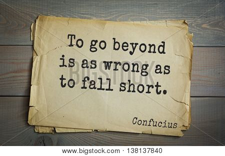 Ancient chinese philosopher Confucius quote on old paper background. To go beyond is as wrong as to fall short.