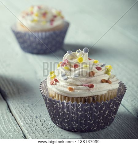 Close up of a nicely decorated cupcakes isolated on light blue wooden boards