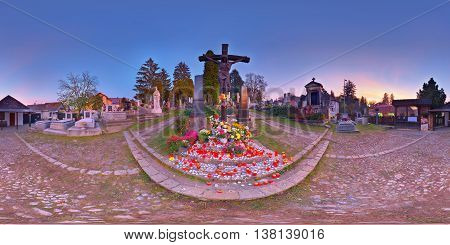TÂRGU MUREȘ, ROMANIA - November 2, 2015: Lots of candles and flowers placed at the base of a crucifix in the Catholic Cemetery at sunset on All Souls' Day, November 2nd, 2015 in Târgu Mureș, Transylvania, Romania.