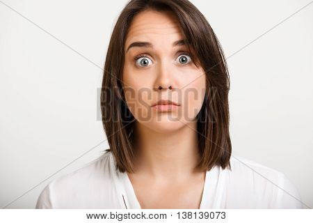 Portrait of young beautiful girl playing ape over white background.