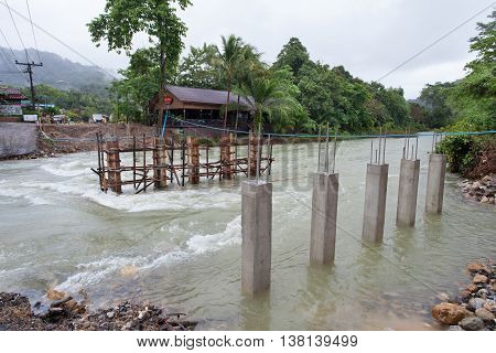 Surat Thane, Thailand-Jun 25 : Cornerstones of the bridge are standing in Khao Sok river that effect from flash flood on Jun 25, 2016 in Surat Thane
