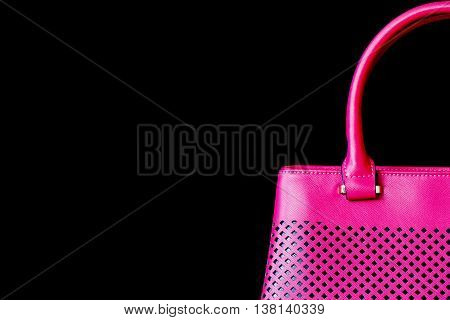 Large part the perforated handbag for women the color of bright fuchsia , texture close-up, dark background. With your place for the text.