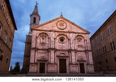 Twilight view of the Pienza Assumption of the Virgin Mary Cathedral with dark blue sky. Facade from white marble. Religious travel destinations background.
