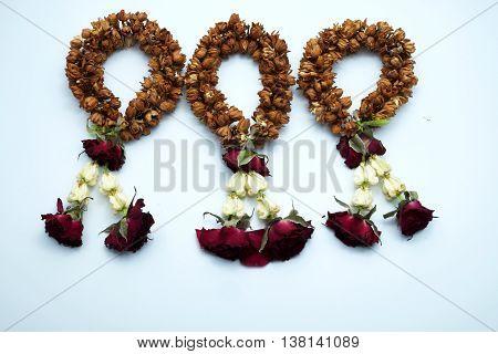 Three dry jasmine garlands on blue background.