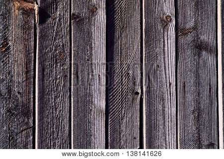 grey vertical aging sunlit wooden wall with harsh shadows