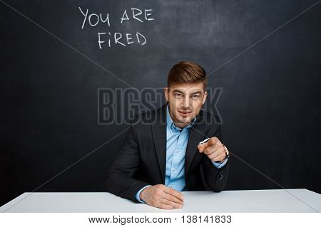image of young suited man point with a finger at the camera over blackboard with a text you are fired