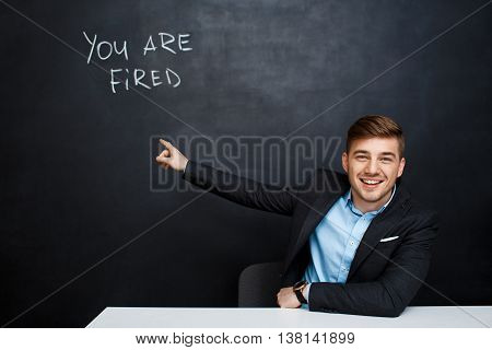image of young suited man point with a finger at the inscription over blackboard with a text you are fired