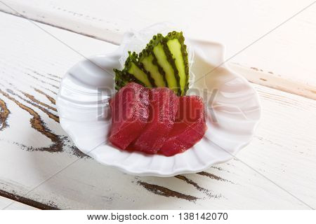 Slices of cucumber and meat. Raw fish on small plate. Fresh ingredients of tasty meal. Sashimi served at local restaurant.