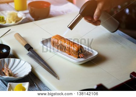 Torch burner over sushi rolls. Man's hand holding torch burner. Chef prepares uramaki sushi. Thermal processing of seafood.