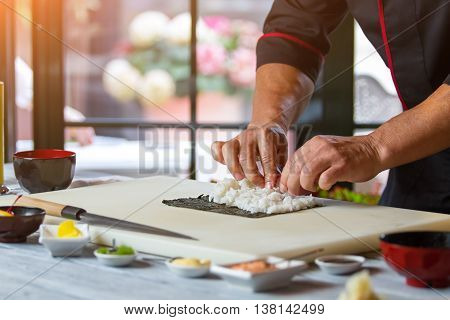 Male hands touch rice. White rice on nori leaf. Basic ingredients for sushi. Kitchen of japanese restaurant.