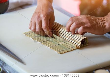 Male hands touch bamboo mat. Small mat on cooking board. Japanese chef at work. Man prepares sushi rolls.