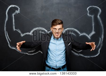 Picture of  angry, mad suited business  man with  fake muscle arms over blackboard.