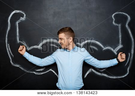 Picture of  funny suited business  man with  fake muscle arms over blackboard. look right