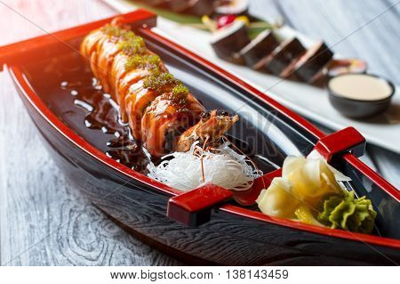Shrimp on sushi boat. Sushi rolls and wasabi. Uramaki rolls with green caviar. Traditional recipe from japanese cuisine.