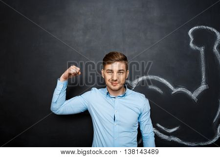 Picture of  funny suited business  man with  fake muscle arms over blackboard.