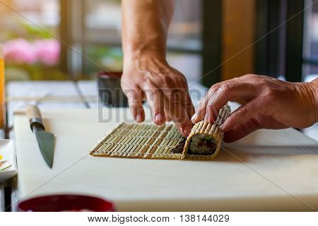 Male hands touch bamboo mat. Knife beside small bamboo mat. How to prepare sushi. Careful hands of cooking teacher.