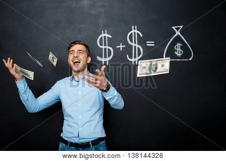 handsome man standing over blackboard. Holding and throwing dollars in his hands and smiling.