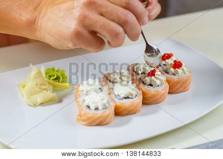Spoon puts caviar on sushi. Small spoon in man's hand. Uramaki rolls with red caviar. Key ingredient for a delicacy.