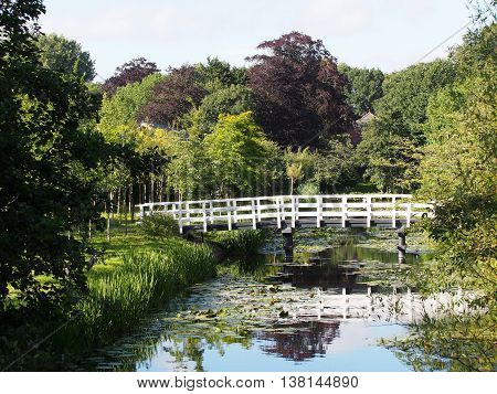 Canal in park land with a white timber bridge The Hague 2016