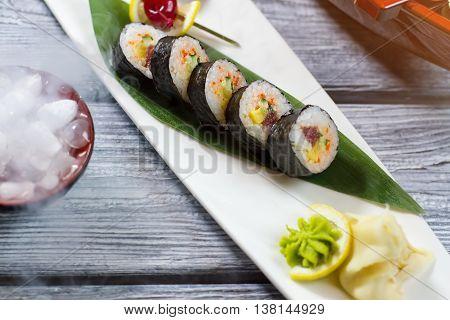 Sushi rolls on green leaf. Wasabi on slice of lemon. Traditional futomaki rolls with tuna. Festive dish at japanese restaurant.