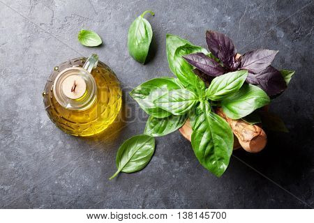 Fresh garden basil herbs in mortar and olive oil on stone table. Top view