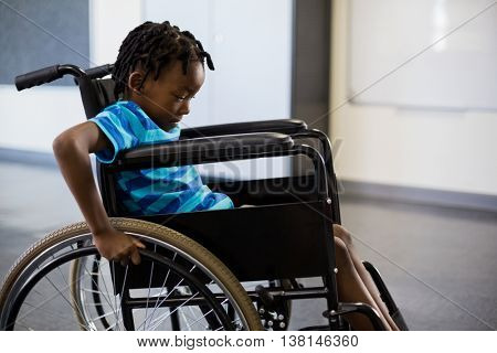 Schoolboy sitting on wheelchair at school