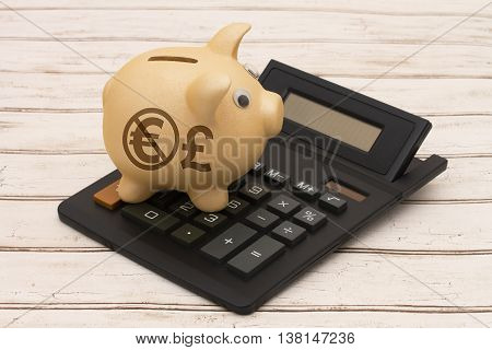 Using the Pound Currency instead of the Euro A golden piggy bank and calculator on a wood background with symbol of the Pound and Euro