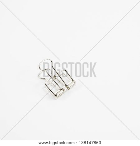 The silver binder clip (paper clip stationery).