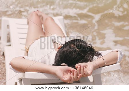 Young beautiful slim girl with brown hair lying on white chaise lounge in the warm summer sea.