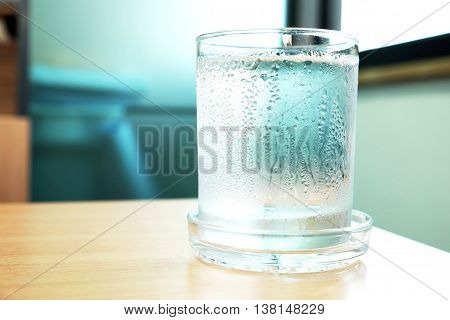 Water in a glass with water drops on wooden table, near the window. Selective focus on glass. Concept of blue-green tone.