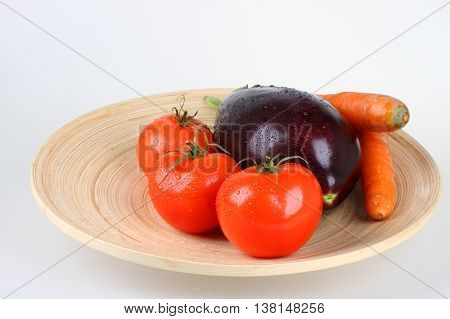 Fresh vegetables on wooden plate,tomatoes,aubergine and carrot