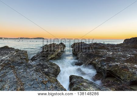 Currumbin Rock Gold Coast clear sky sunrise with incoming ocean rushing through the rocks