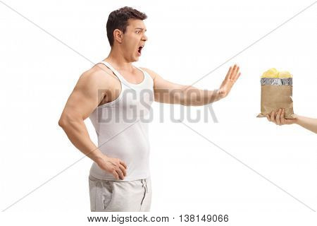 Studio shot of a young man refusing potato chips isolated on white background