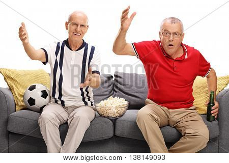 Two displeased seniors watching a game of football and gesturing with their hands isolated on white background