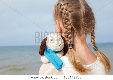 Children psychology. The little beautiful girl embraces an amusing dog - toy. Favorite soft toy. seen from behind