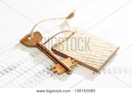 Key attached to blank tag with rope on paper background with digits