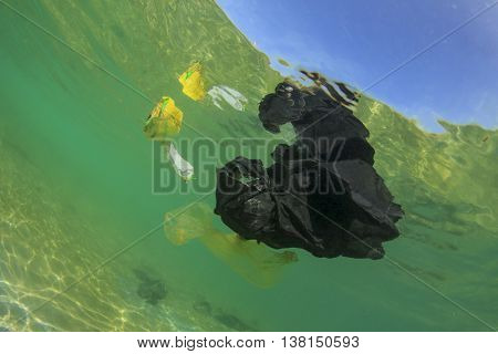 Plastic bag rubbish causes water pollution in ocean. Shows need for recycling.