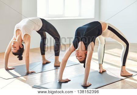 Two Young Women Doing Yoga Asana Upward Bow (wheel) Pose